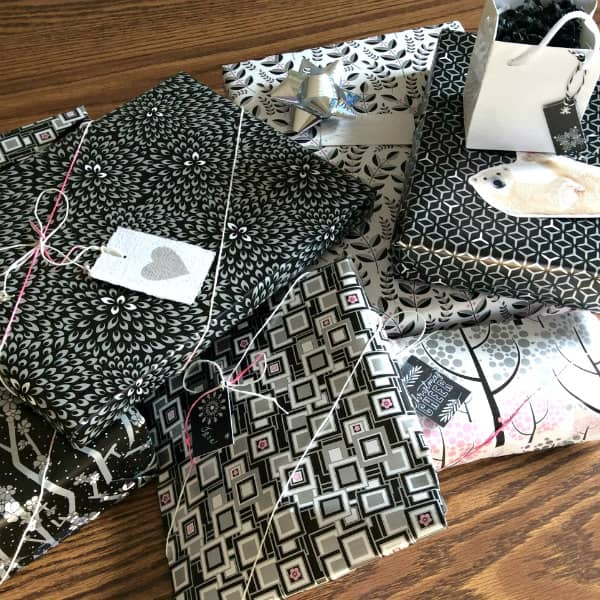 gifts wrapped in black, white, pink and silver patterned papers