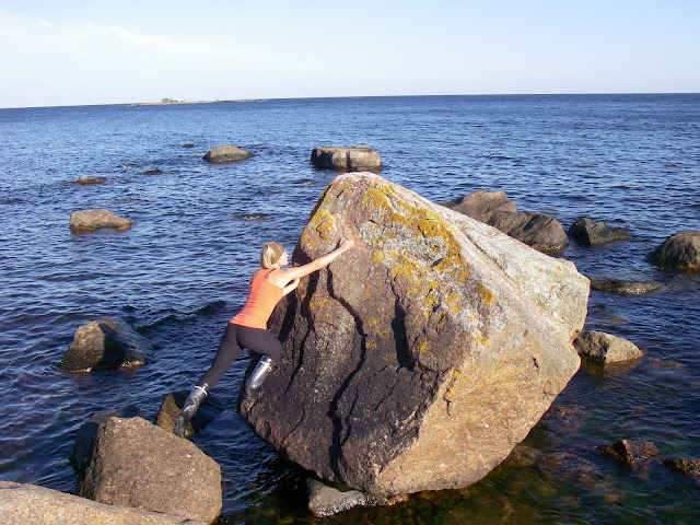 siirtolohkare rannassa, ihminen kiipeää kivelle