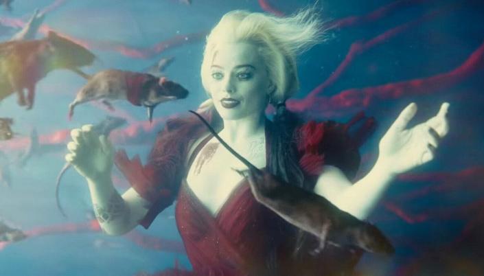 Imagem: cena do filme com a personagem Arlequina, em seu vestido vermelho, cabelos loiros presos em duas tranças longas tingidas de preto e vermelho, afundando debaixo da água, e diversos ratos nadando em torno dela.