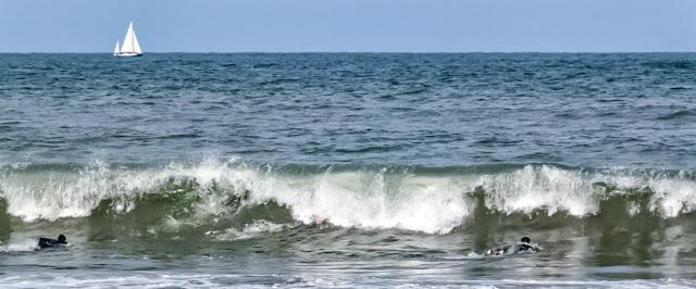 Velero en el horizonte y nadadores a las olas del mar.