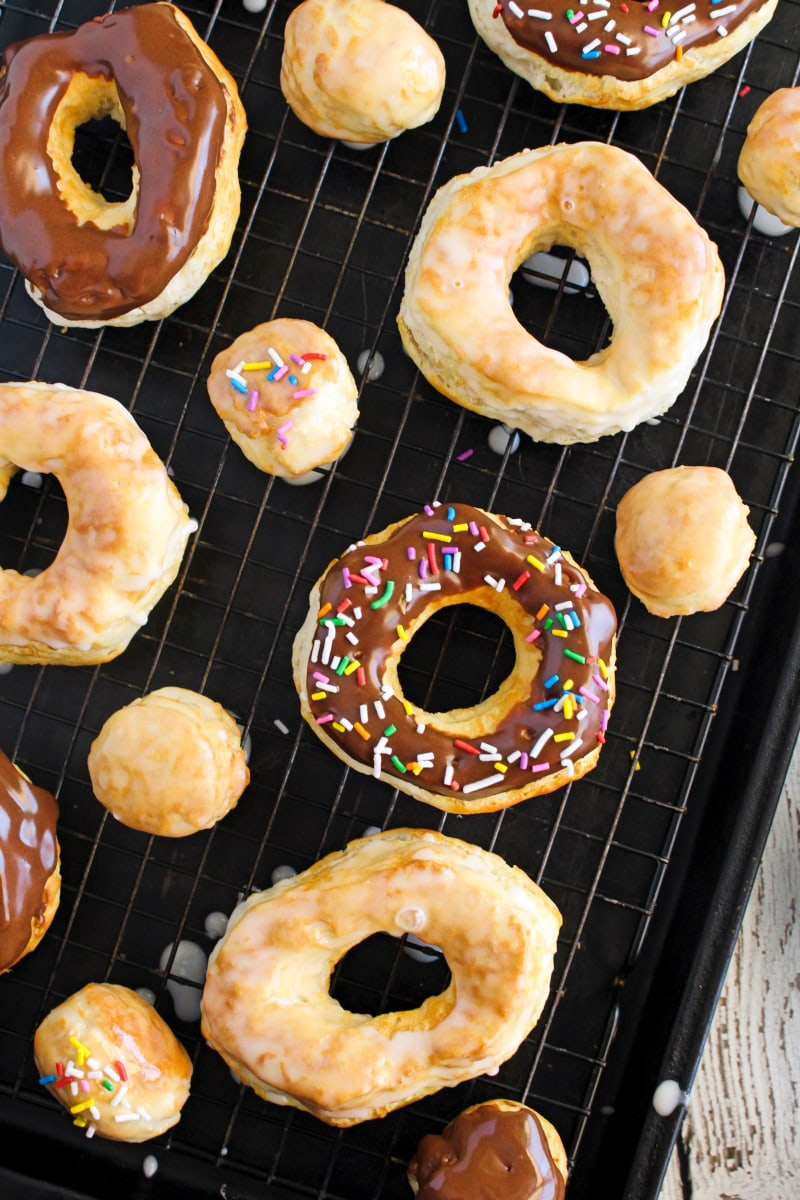 An overhead photo of a variety of chocolate dipped donuts with sprinkles, glazed donuts, and donuts holes on a wire rack over a baking sheet.