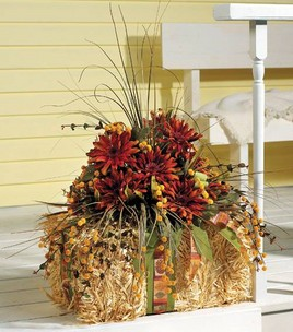 This hay centerpiece with dark orange and red flowers is great for autumn.