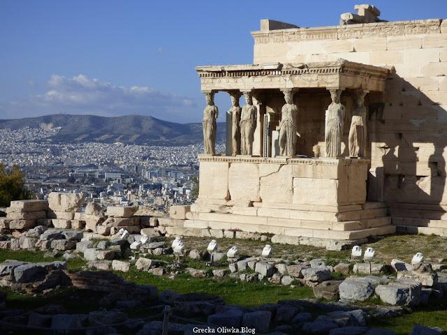 Ruiny starych budowli, po prawej stronie Kariatydy , po lewej widok na miasto Ateny.