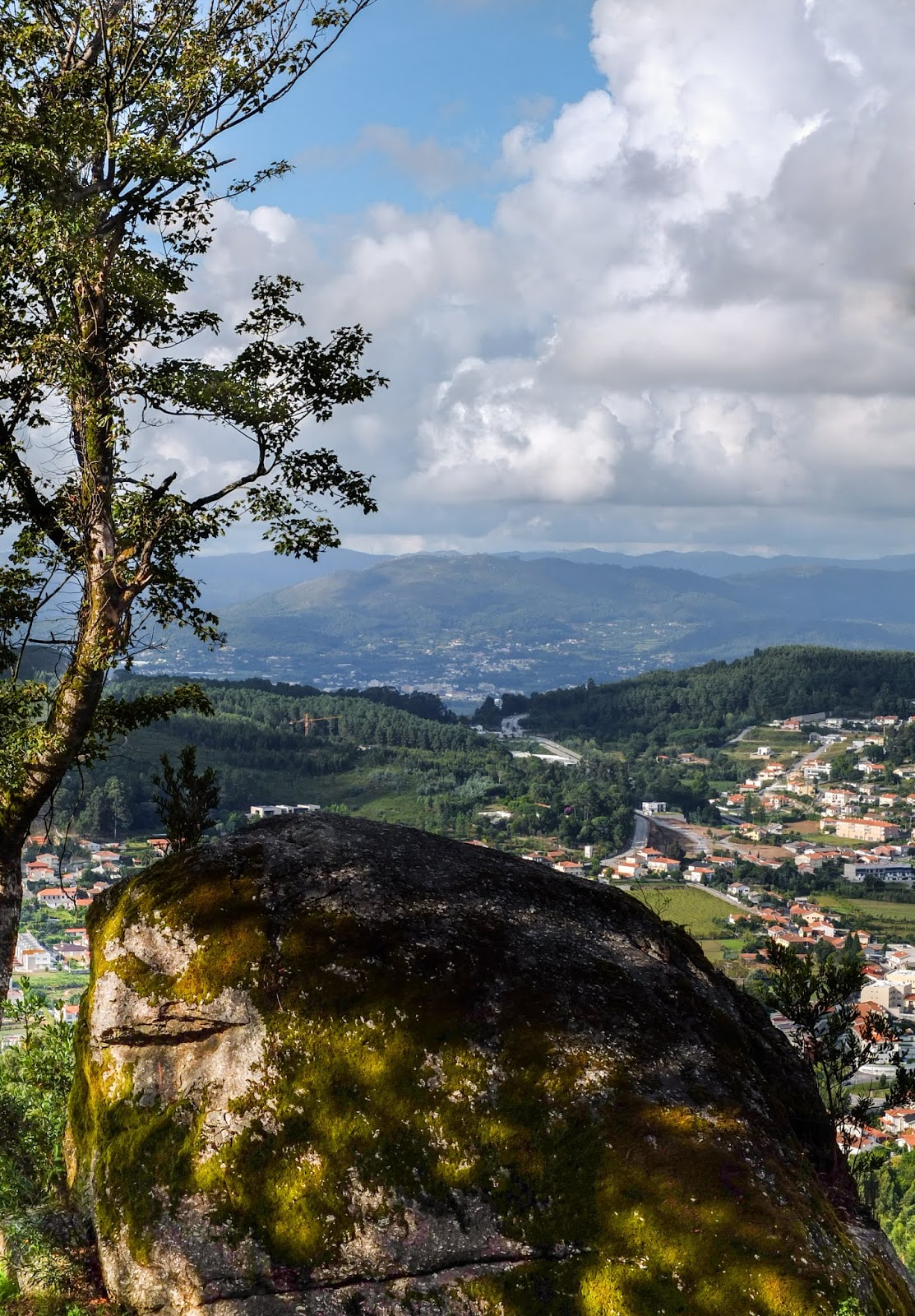 A giant rock on the hillside of the Espinho Mountain in Portugal with mountain views.