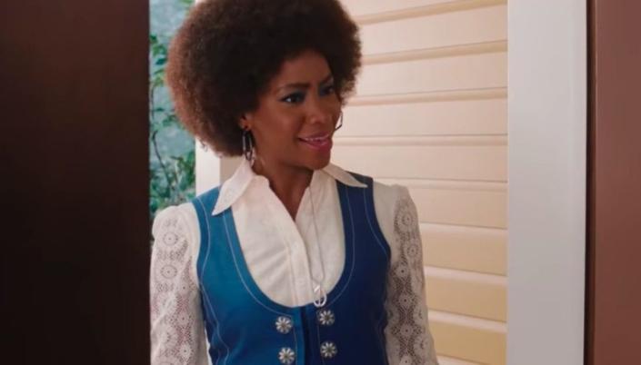 Imagem: Monica Rambeau, ainda como Geraldine, uma mulher negra e sorridente, com uma roupa branca com um colete azul, brincos redondos e um colar prateado com um pingente prateado com formato de um círculo e uma espada, na entrada da porta de uma casa.