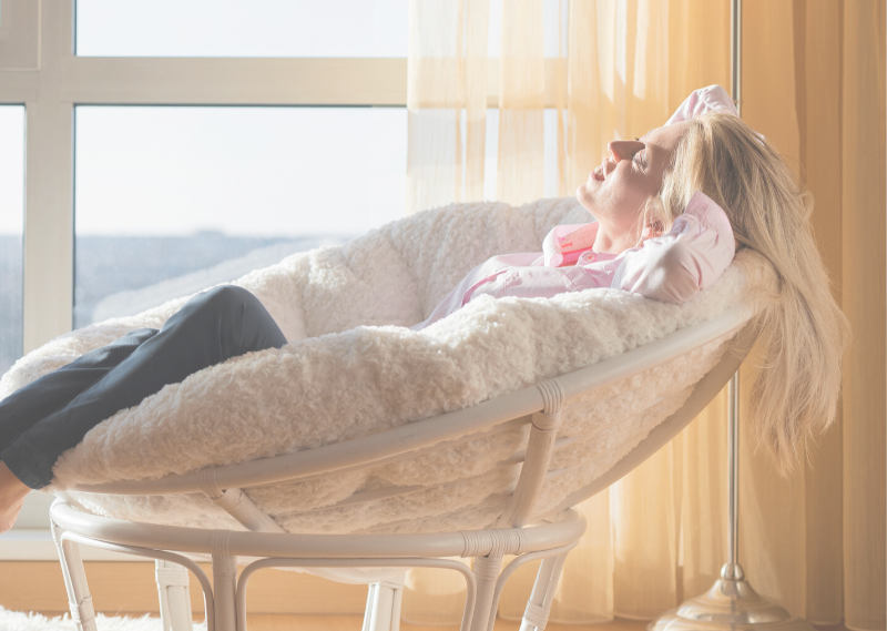 Lady sitting on a chair relaxing in a post about five ways how not to feel guilty for having a lazy day.