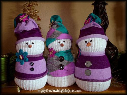 three DIY sock snowmen on a shelf