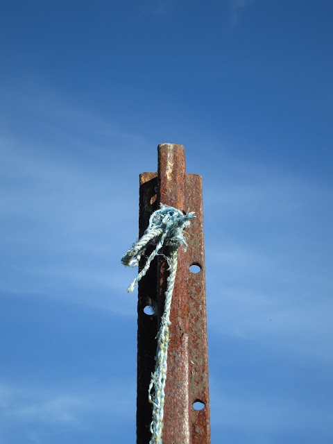 Frayed blue nylon rope tied through hole on rusty pole in front of deep blue sky