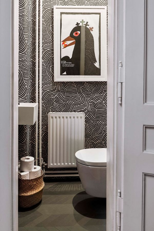 Sophisticated powder room with black and white wallpaper