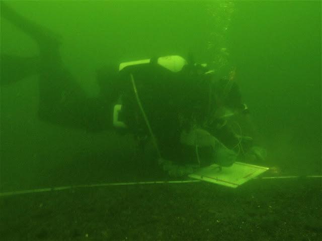 Sukeltaja sukelluslinjalla, tekee muistiinpanoja.