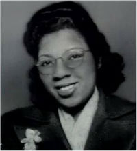 Headshot of a young Black woman wearing a blouse and jacket, eyeglasses, and hair styled in a laite 1940s coif