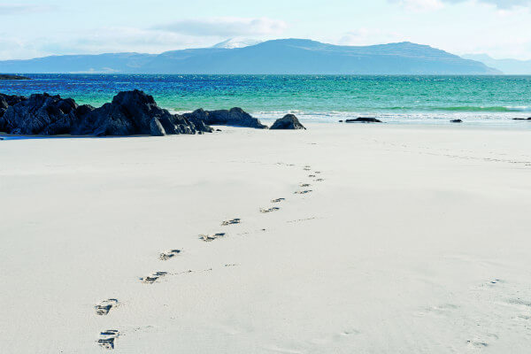 Isle of Iona beach with rocks, blue-green water, and footprints in the sand