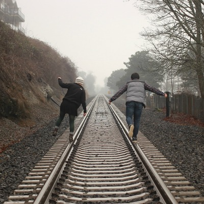 A man and a woman walking down straight railway tracks, balancing on the rails