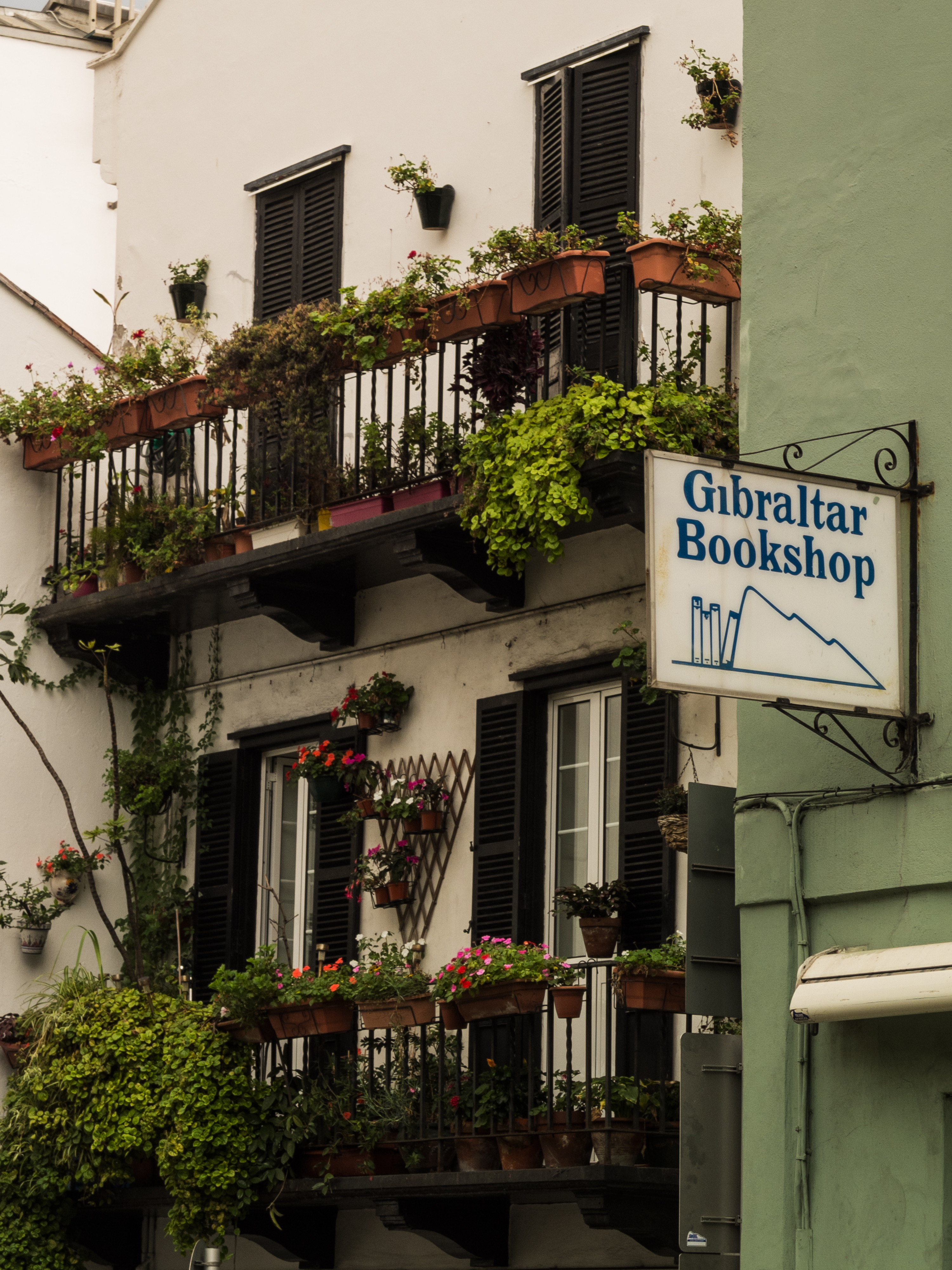 A sign for the Gibraltar Bookshop on the side of a green building.