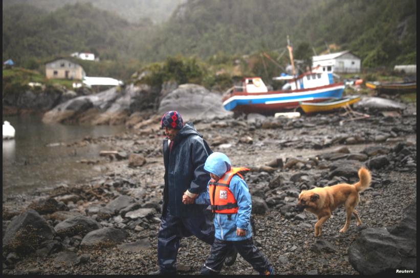 Un hombre y su hijo en el pueblo de Sotomó, Chile, se dirigen a una escuela primaria el 6 de agosto de 2021. La comunidad ha recibido el servicio de internet gratis mediante un programa del multimillonario estadounidense Elon Musk / REUTERS