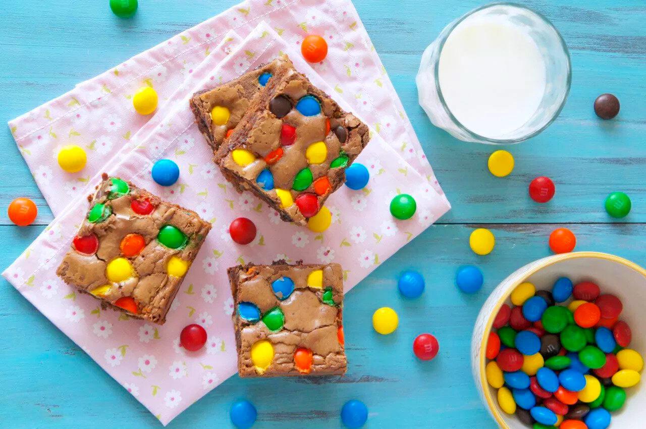 Fatias de Brownie de M&M's próximo a um copo de leite