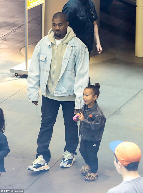 Doting dad Kanye West holds North