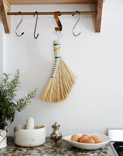 open shelving in kitchen with brass hooks on bar and hanging Japanese whisk broom