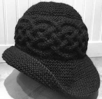 Black hat with Celtic cables and brim knitted with Knit Picks Wool of the Andes