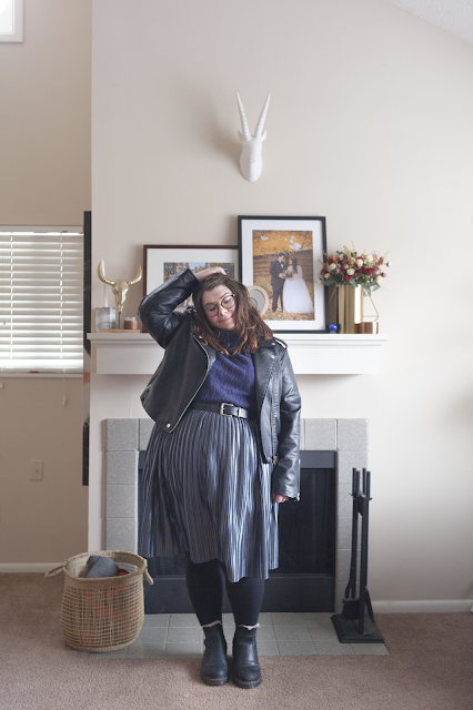 An outfit consisting of a black moto jacket, navy blue sweater and silver pleated midi skirt.