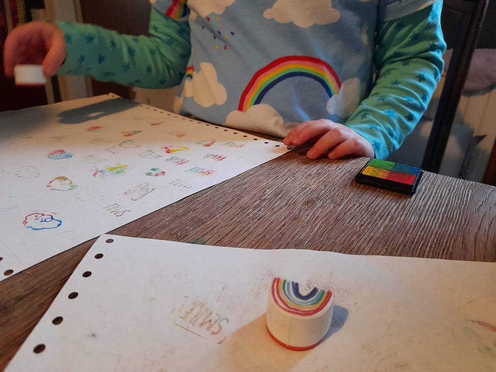 Child using rainbow stamps to cover a sheet of paper