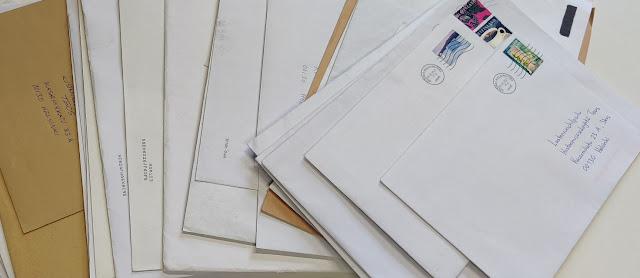 Kirjekuoria pinossa pöydällä.