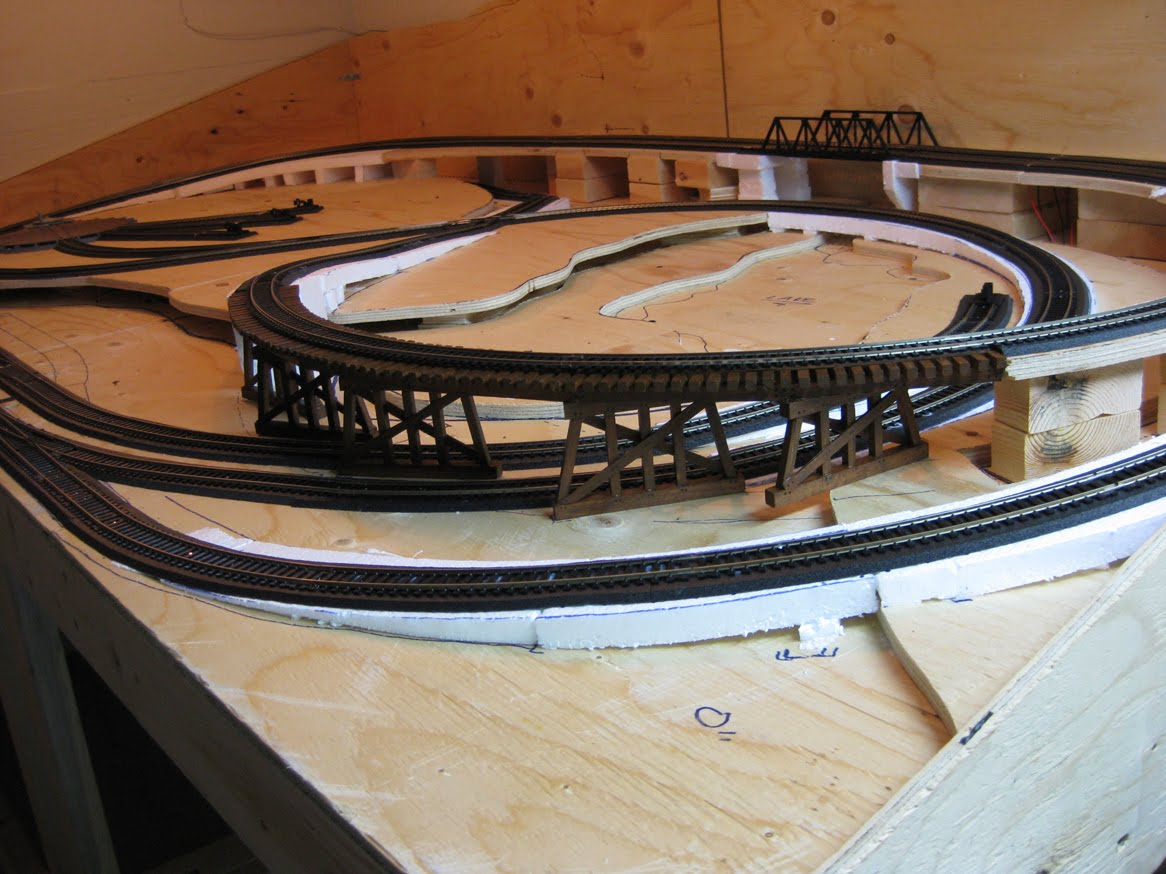 Model railroad benchwork with completed track on foam roadbed and painted wooden train trestle
