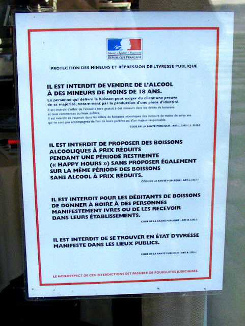 Obligatory legal notice on the door of a restaurant about the serving and consumption of alcohol.  Indre et Loire, France. Photographed by Susan Walter. Tour the Loire Valley with a classic car and a private guide.