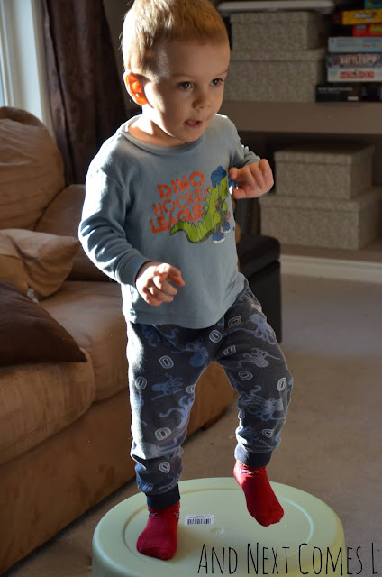 Toddler stomping on a large plastic bucket