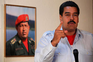 Nicolás Maduro speaks with a photo of the late Hugo Chávez in the background