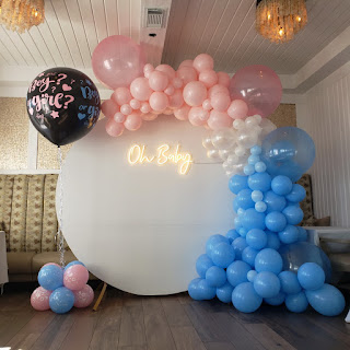 White backdrop, pink and blue balloon arch, gender reveal big balloon with blue and pink confetti & small balloons
