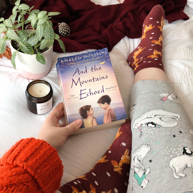 Front cover of 'And the Mountains Echoed' next to an unlit candle, small green plant and pajama leg