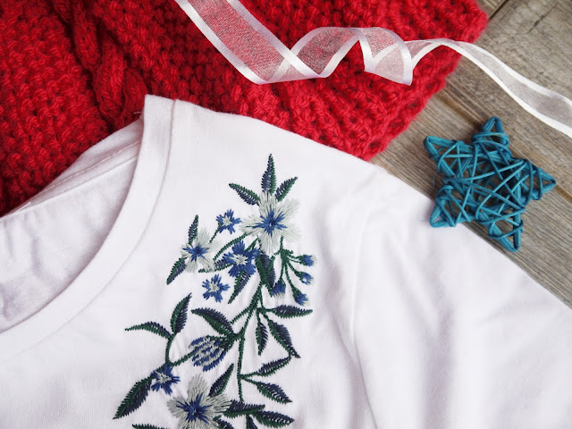 a pink knitted hat and a white tee shirt with blue and green floral embroidery