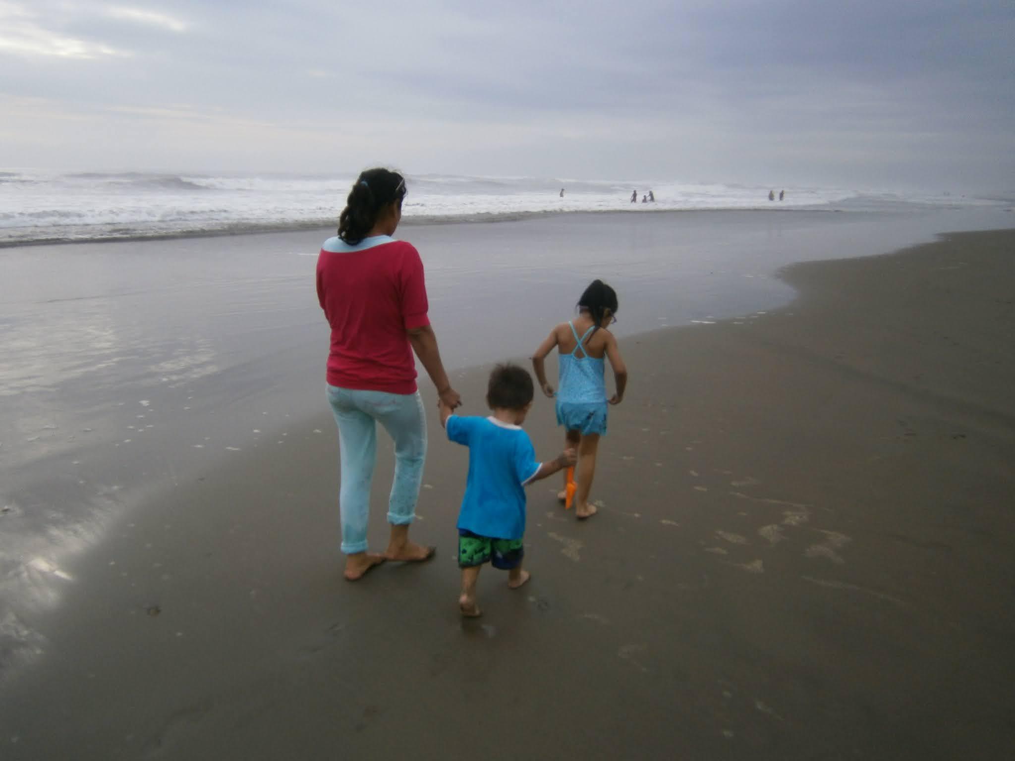 Mujer caminando sobre la orilla de la playa y acompañado de niños