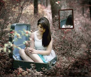 Chica dentro de maleta en un bosque