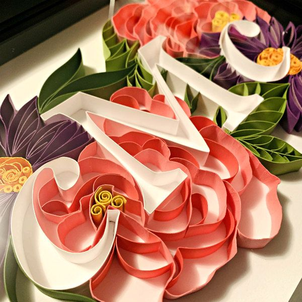 close up of on-edge paper strips arranged into floral design with initials