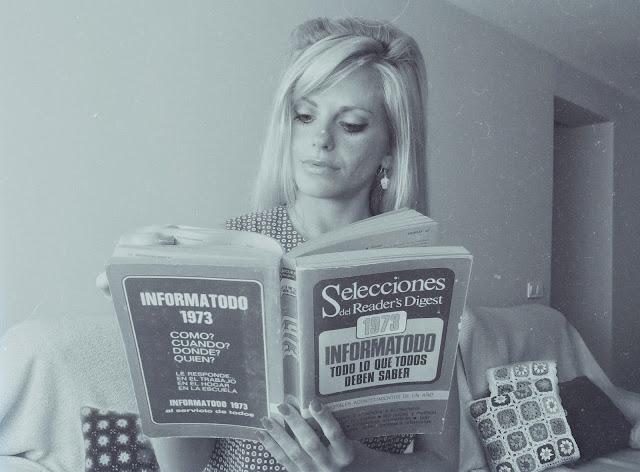Alejandra Colomera leyendo un libro original del año 1973, llamado Informatodo de Reader's digest. La imagen está en blanco y negro