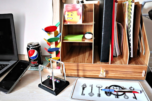 One side of the desk, with a large wooden desk organiser, with space for pens and files and a drawer beneath, as well as a Newton's Cradle, Coke can and battered mobile phone