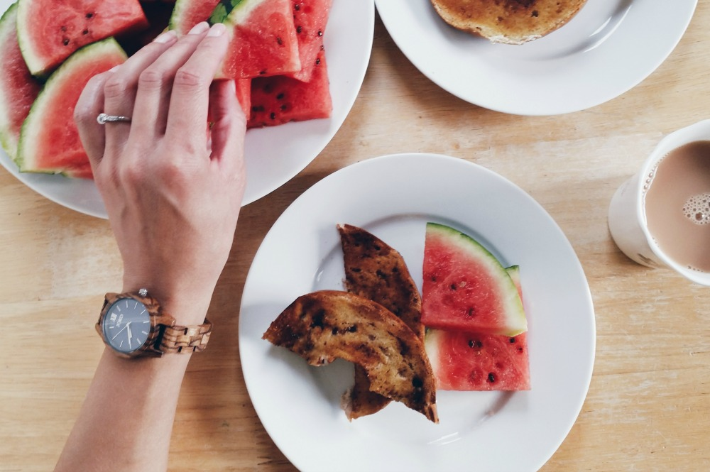hand-wearing-jord-frankie-35-zebrawood-navy-watch-reaching-for-a-plate-of-watermelon
