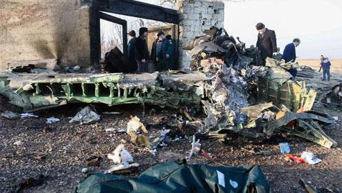 Orang-orang berdiri di dekat reruntuhan setelah sebuah pesawat Ukraina yang mengangkut 176 penumpang jatuh di dekat bandara Imam Khomeini.