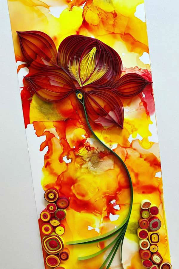 quilled red floral design on alcohol ink background