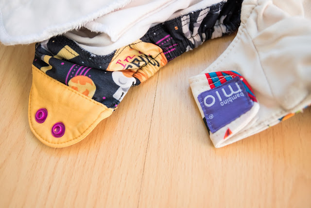 close up of cloth nappy fastenings with poppers and velcro