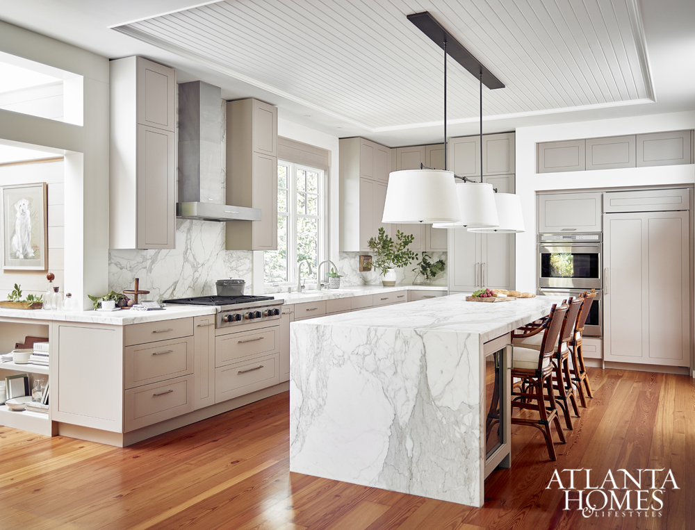 Gorgeous white ktichen with marble waterfall edge island and wood floors
