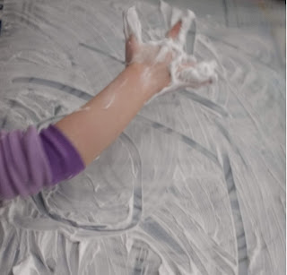preschool aged child writing in shaving cream