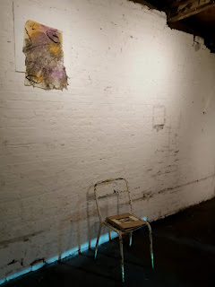Installation includes old chair, folder of railway news clippings, charcoal space left behind and frottage collage.