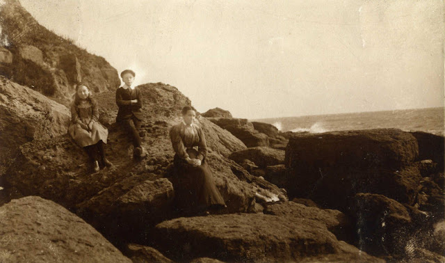 2 children and their mother on rocks