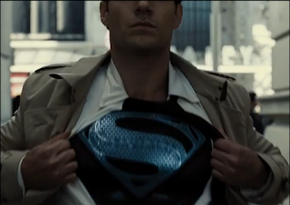 Shot of Clark Kent opening up his shirt to reveal his black suit and silver S-shield underneath.