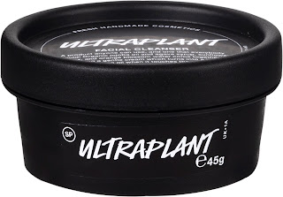 A cylindrical short black pot filled with pale liquid with a black rectangular label on the side that says lush ultra plant in white font with a circular black lid with a circular black label with lush ultra plant facial cleanser in white font on a bright background
