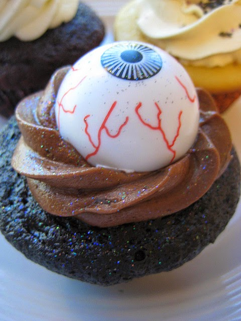 Chocolate cupcake with chocolate icing frosting and eyeball decoration sprinkled with glitter