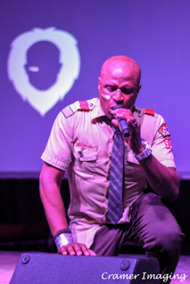 Cramer Imaging's professional quality concert photograph of Alex Boyé in scout uniform singing with logo in background in Firth, Idaho
